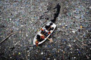 barca sobre basura flotante oceano